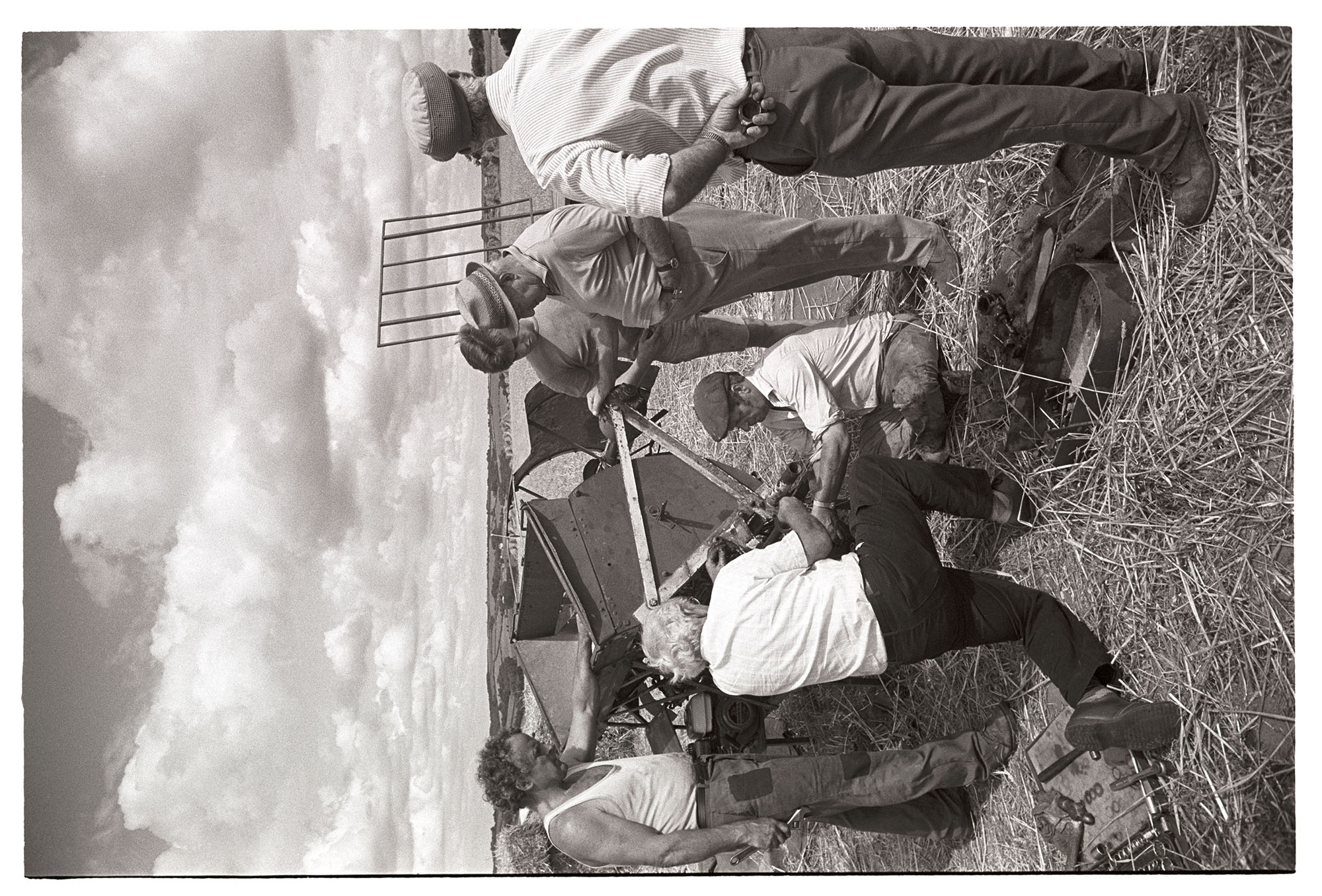 Reed combers mending fault in tying machine attached to reed comber. <br /> [Men fixing the tying machine attached to a reed comber in a field at Spittle, Chulmleigh, while they are harvesting.]