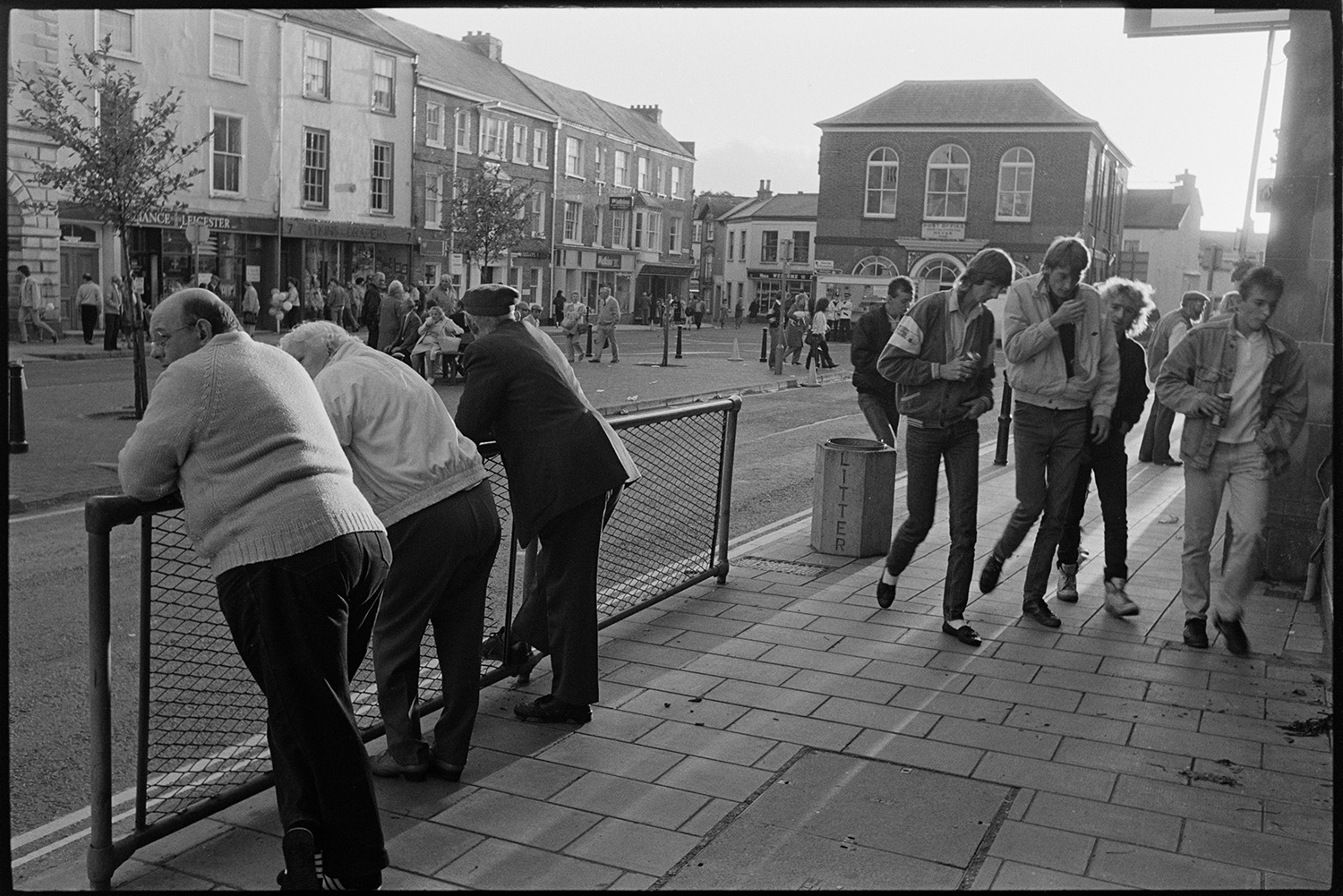 Spectators waiting for start of fair in town square. <br /> [Three people leaning on railings opposite South Molton Town Hall waiting for the fair to start. A group of young men are walking past carrying cans of drink. More people are gathering for the fair further along the street, outside shop fronts.]