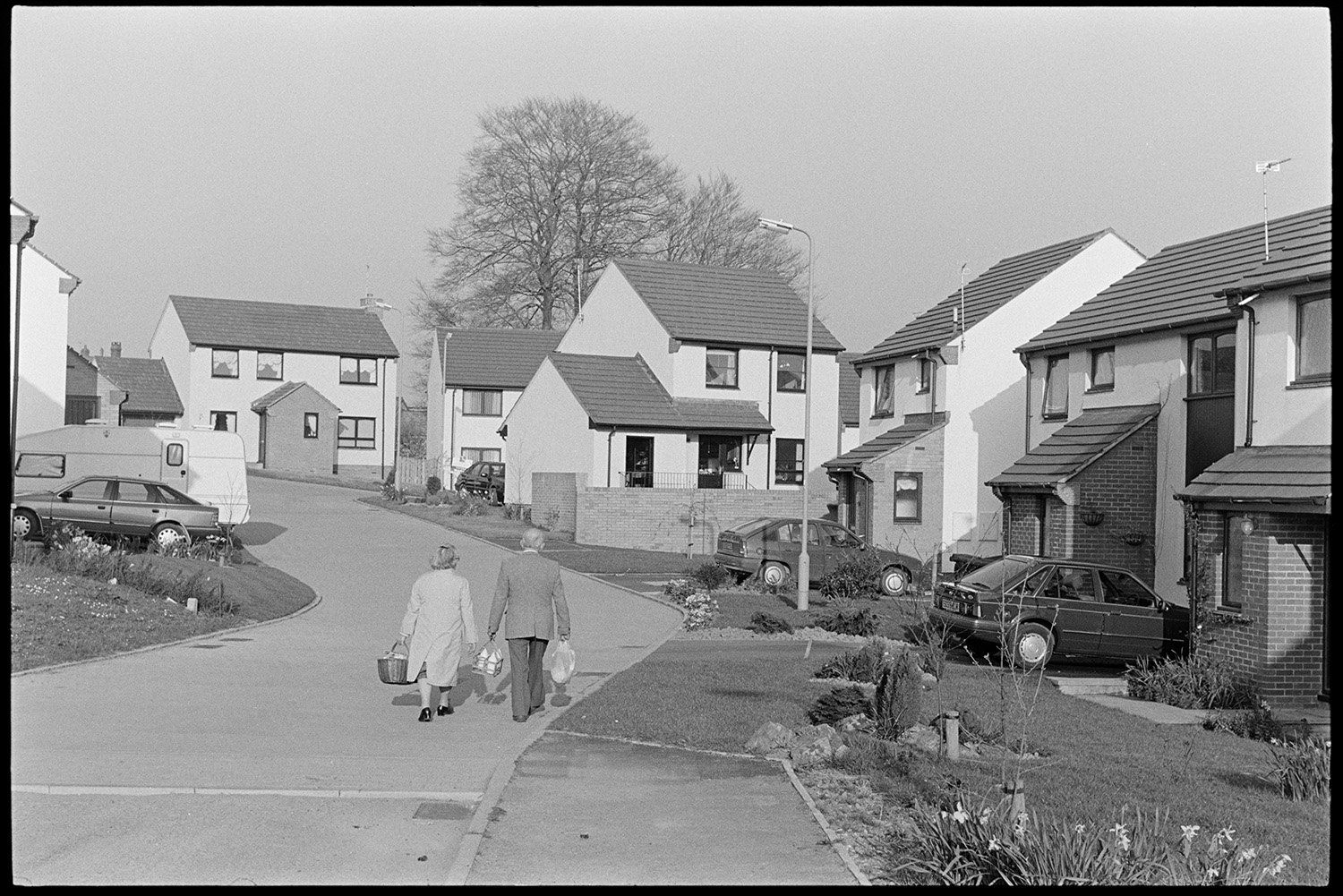 New housing estate. <br /> [A man and woman carrying shopping bags and walking through a new housing estate in South Molton. Cars are parked in the driveways of the houses.]