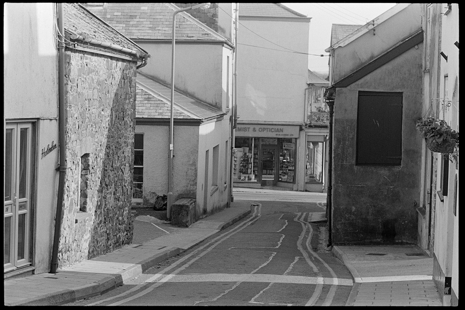Street scenes. <br /> [A side street in South Molton. The shop front of a chemist and optician can be seen opposite the road junction at the end of the street.]