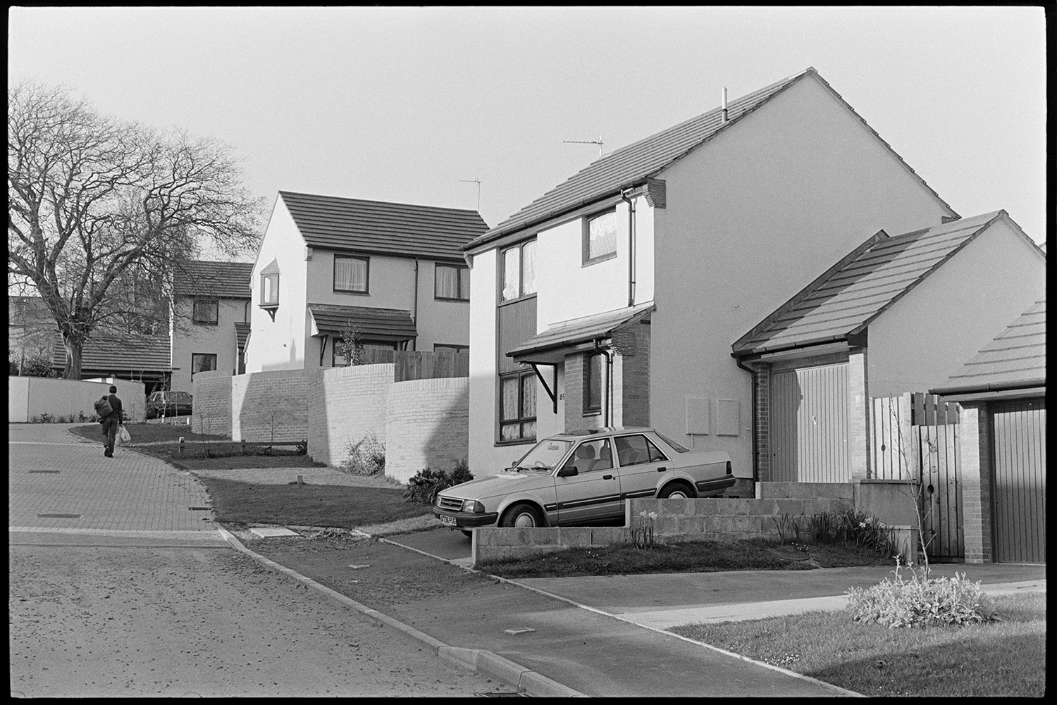 New housing estate. <br /> [Houses on a new housing estate in South Molton. A car is parked on the driveway outside one house and a person is walking up the hill of the estate in the background.]