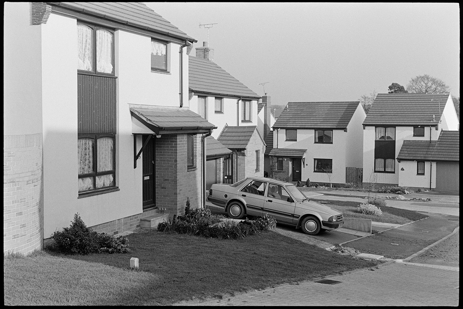 New housing estate. <br /> [Houses on a new housing estate in South Molton. A car is parked in the driveway of the house in the foreground.]