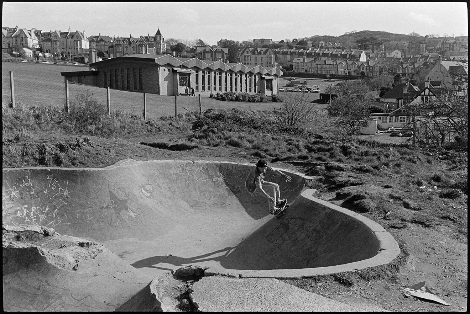 Skateboarders at skate park near sea. <br /> [A skateboarder skating on a concrete ramp at a skate park in Ilfracombe. The town of Ilfracombe can be seen in the background.]