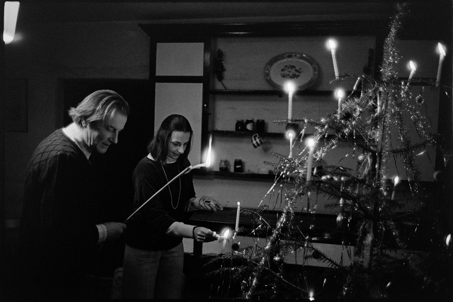 Couple lighting candles on Christmas Tree.<br /> [Pat Furse and Antonia Furse lighting candles on a Christmas tree in a darkened room, in Halsdon, Dolton. Pat Furse is holding a long taper.]