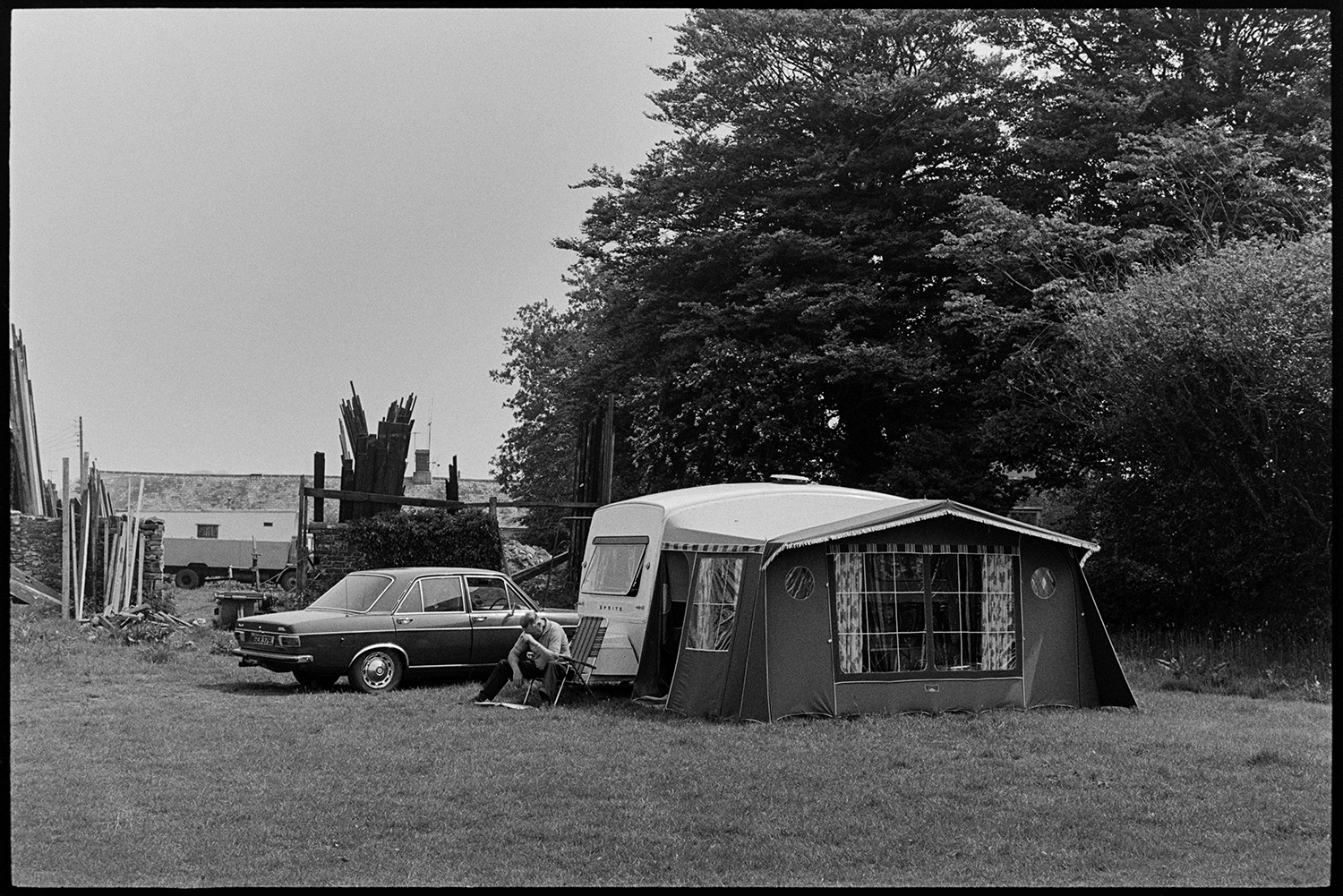 Caravan and tent on pub site. <br /> [A person sat outside a caravan with an awning next to a parked car in the grounds of the Royal Oak pub, Dolton.]