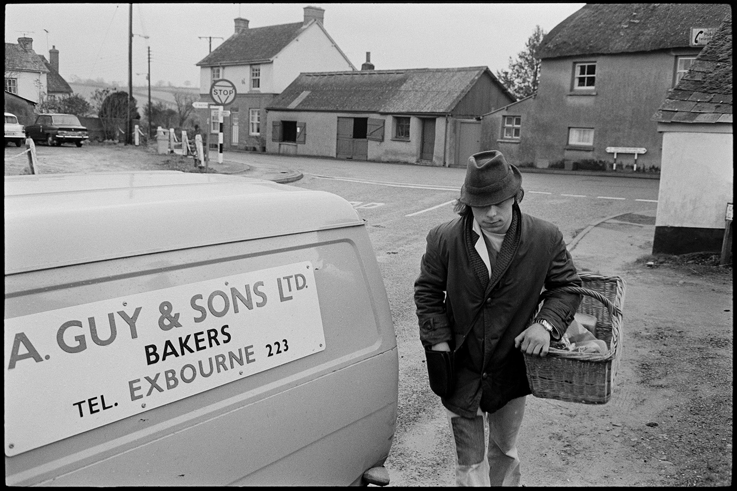 Baker delivering bread round village from van. <br /> [A baker delivering bread in Monkokehampton. He is carrying a basket and walking past an A Guy & Sons Ltd of Exbourne baker's van. Houses can be seen in the background.]
