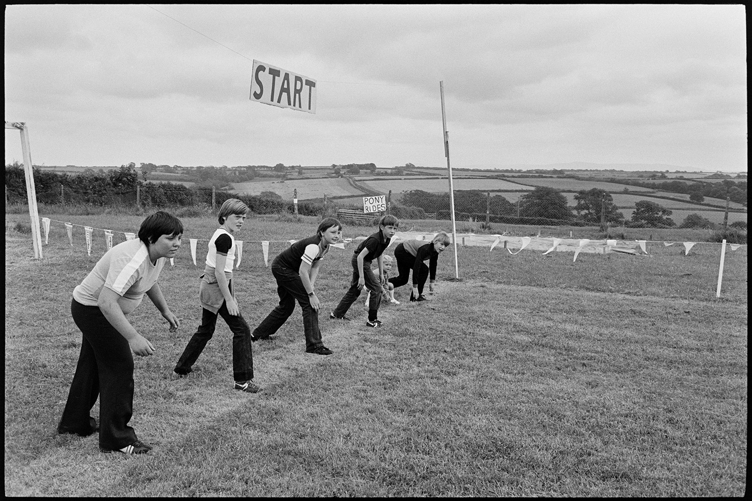 Sports, start of race for boys. <br /> [Boys at the start line of a running race in a field at Roborough Sports Day. A sign reading 'Pony Rides' is in the background.]