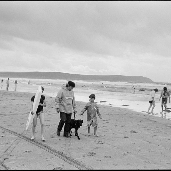 Man & boys walking along beach, dog, Woolacombe, August 1982. Documentary photograph by James Ravilious for the Beaford Archive © Beaford Arts
