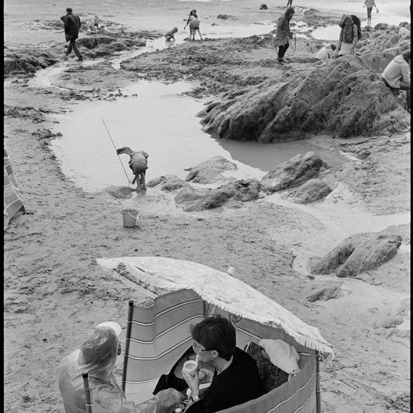 People drinking tea in shelter, wind-break, on beach, Woolacombe, August 1982. Documentary photograph by James Ravilious for the Beaford Archive © Beaford Arts