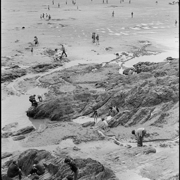 People on beach, rocks, Woolacombe, August 1982. Documentary photograph by James Ravilious for the Beaford Archive © Beaford Arts