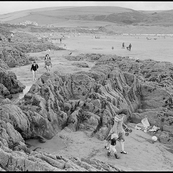 People on beach, rocks, woman & child, Woolacombe, August 1982. Documentary photograph by James Ravilious for the Beaford Archive © Beaford Arts