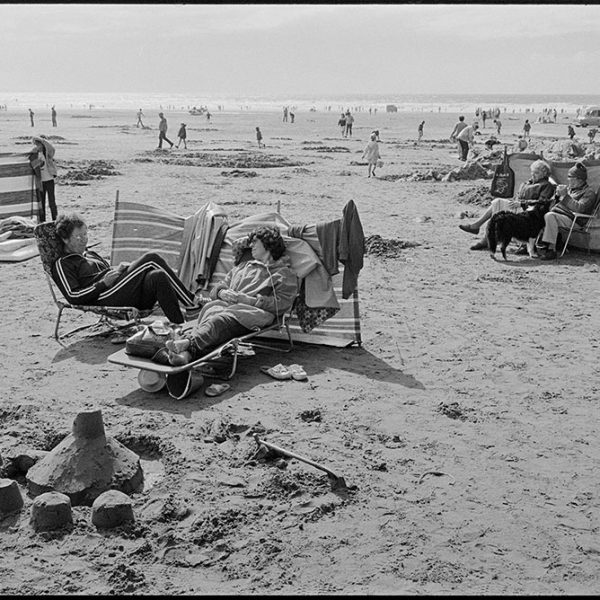 Beach scenes, people sitting behind windbreaks, Woolacombe, August 1982. Documentary photograph by James Ravilious for the Beaford Archive © Beaford Arts