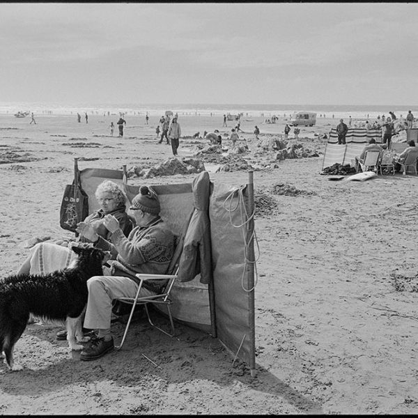 Beach scenes, couple sitting behind windbreak, Woolacombe, August 1982. Documentary photograph by James Ravilious for the Beaford Archive © Beaford Arts